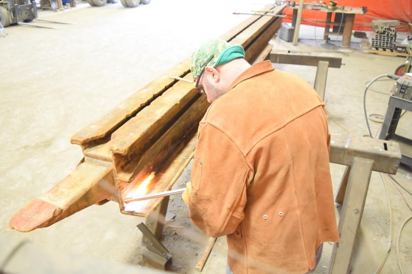 Steve Vansant of TrenchTech repairs cracked welds in a slide rail linear post.