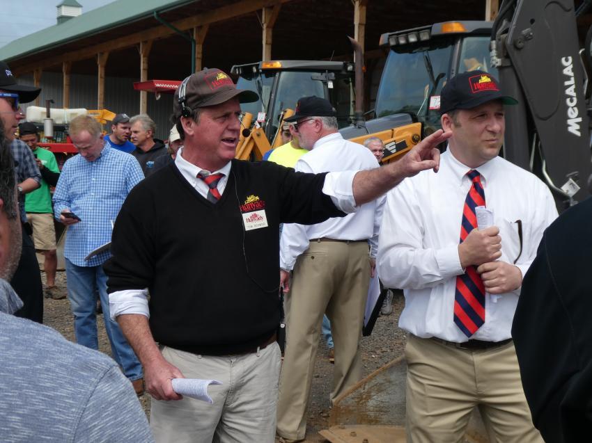 Hunyady Auctioneer Tim Schwer (L) and Ringman Tim Dewey take bids on a Case backhoe loader.