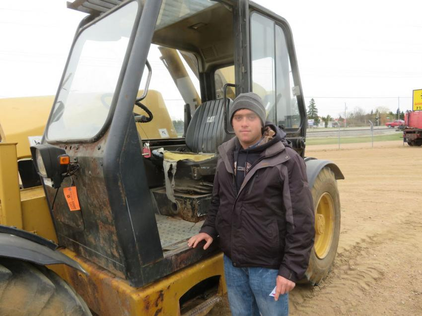 Harold Shirk of Leon Shirk Equipment inspects a Cat TH63 telehandler.