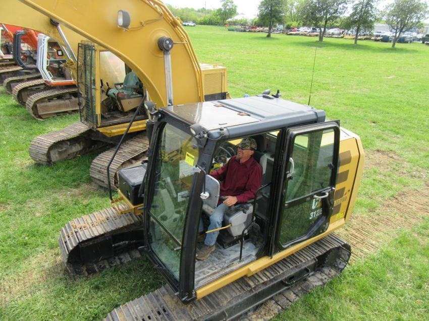 John Kananen of Real Tree Lumber & Mats gives a Cat 312E L excavator a thorough run-through while considering a bid.
