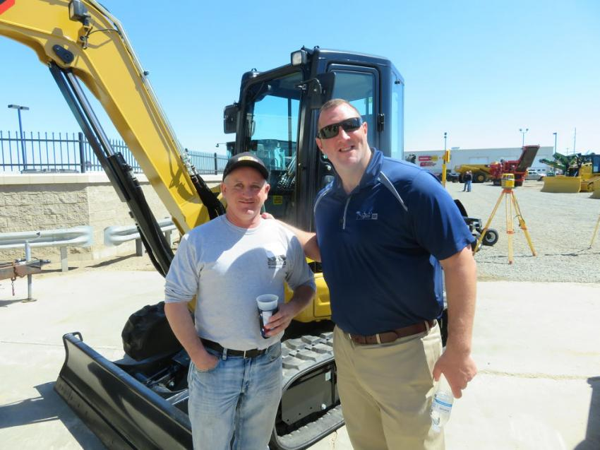 Ben Knepper (L) of Fabick Cat shows a Cat 305.5 mini-excavator to Andy Hagen, owner of Andy Hagen Excavating.
