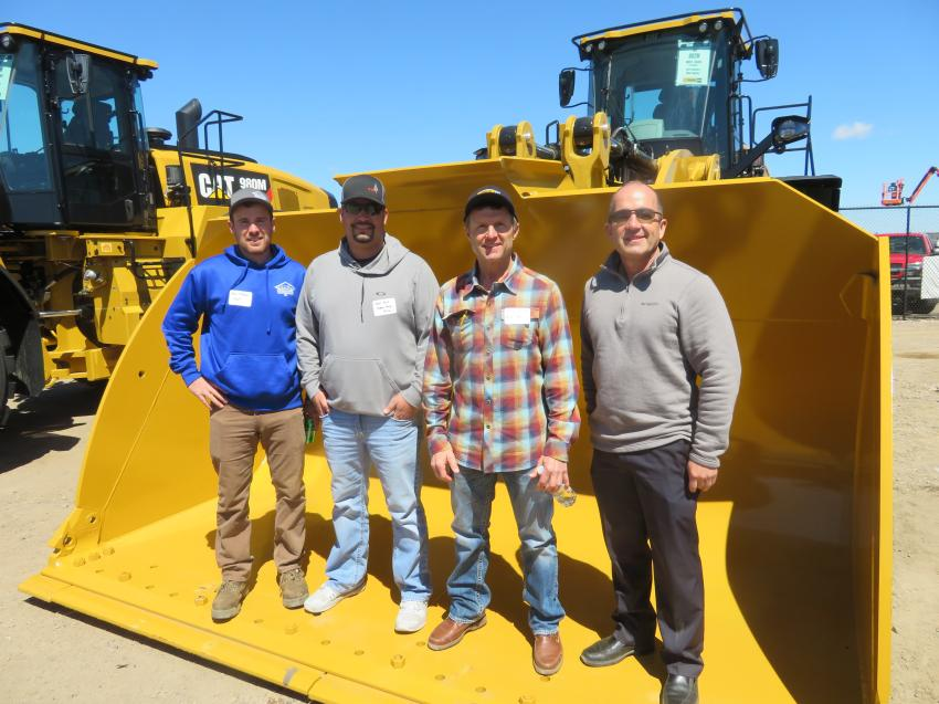 Standing in the bucket of a Cat 982M wheel loader (L-R) are Paul Mumm of Stout Construction; Sam Rud of Signal Peak Silica; Terry Pecha of A-1 Excavating; and Tom Scalzo of Fabick Cat.