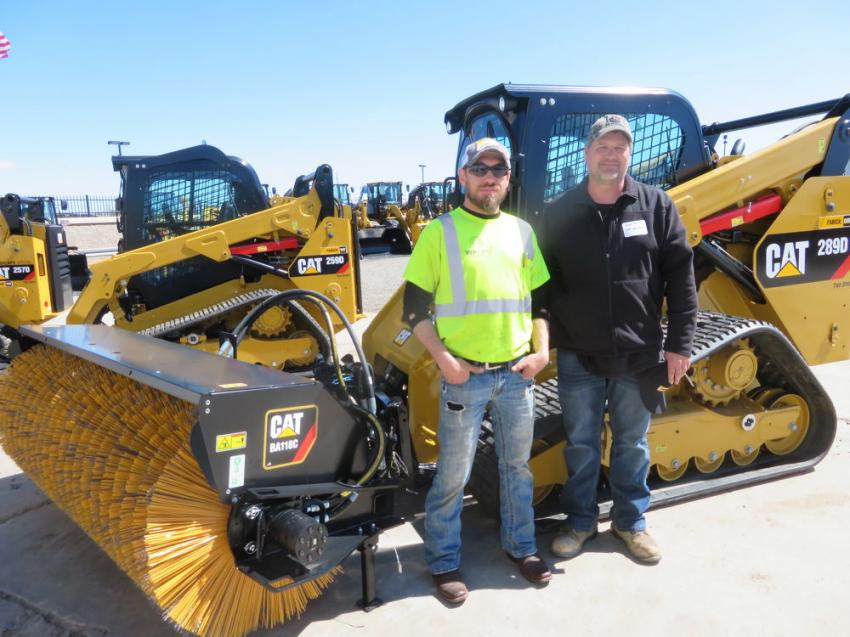 Sean Tracy (L) and Scott Mercer of W.P. Operations look over a Cat 289D track skid steer equipped with a Cat BA118C broom.