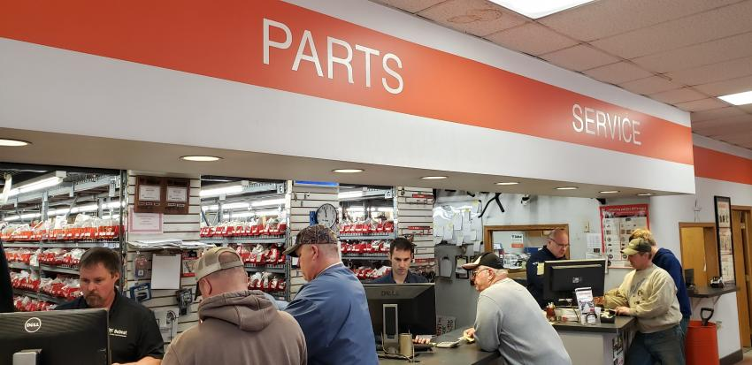 (L-R, behind counter): Dan Cox, service manager from Farm-Rite of Willmar, Minn., helps out with the parts special at the Dassel open house, lending a hand at the counter to Ron Daniels, Farm-Rite parts manager, and Tom Cox, Farm-Rite service manager and co-owner.