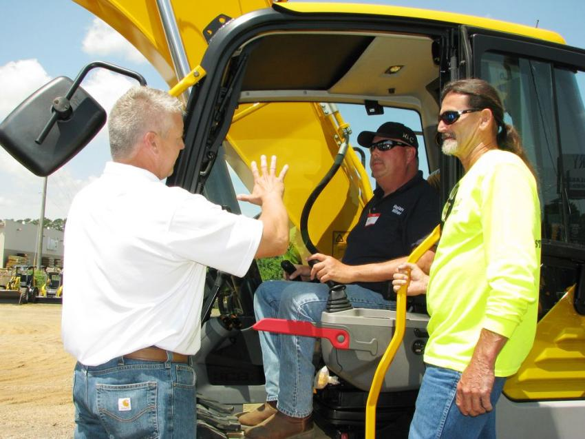 Jarrod Plunkett (L), JCB of Alabama goes over some of the newest features on the JCB 220X LC excavator with Kevin Carter (in cab) of the Ragland Alabama Water Department and Paul Davis of the Ragland Alabama Street Department.