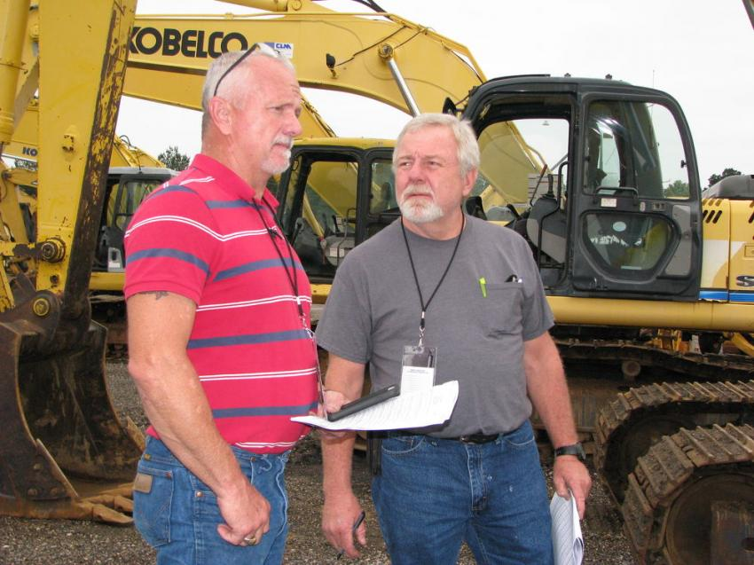 Discussing what excavators they plan to bid on are Chris Jones (L) and Jimbo Sullivan of Tim Jones Auto Truck & Tractor, Mendenhall, Miss.