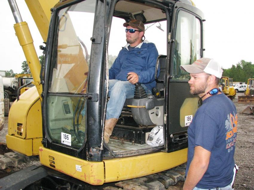 Testing hydraulics and operation of some of the mini-excavators prior to sale time are John Steube (in cab) and Parker Bourque of Southern Lawncare & Excavation, Saucier, Miss.