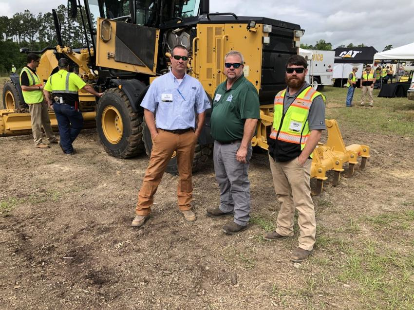 T.J. Savarese and Greg Johnson (both of Cleland Site Prep in Hilton Head, S.C.) talk with Greg Clark of Blanchard Machinery about the tight turning radius of the new Cat 120 all-wheel drive motograder.