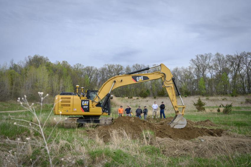 Attendees watch as an operator tries out the Cat 323F hydraulic excavator in the testing field.