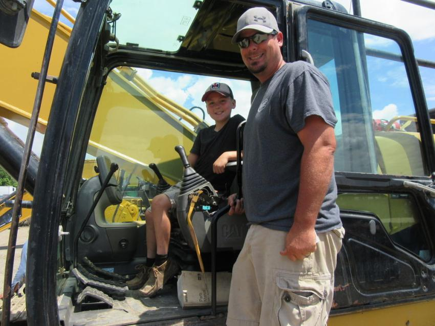 Jason Roberts of Roberts Paving and son, Grady, try out a Cat 345C L excavator at the auction.