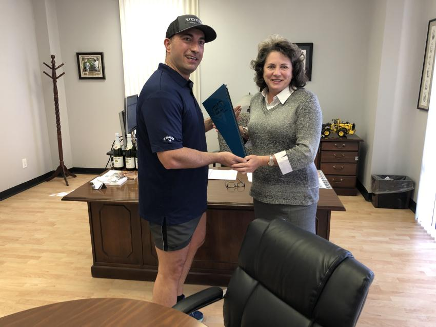 After completing his run, Mario Stoilovich, director of business development, presents the 60-year torch to Kristin Parker, regional general manager of North Carolina, at the Charlotte branch.