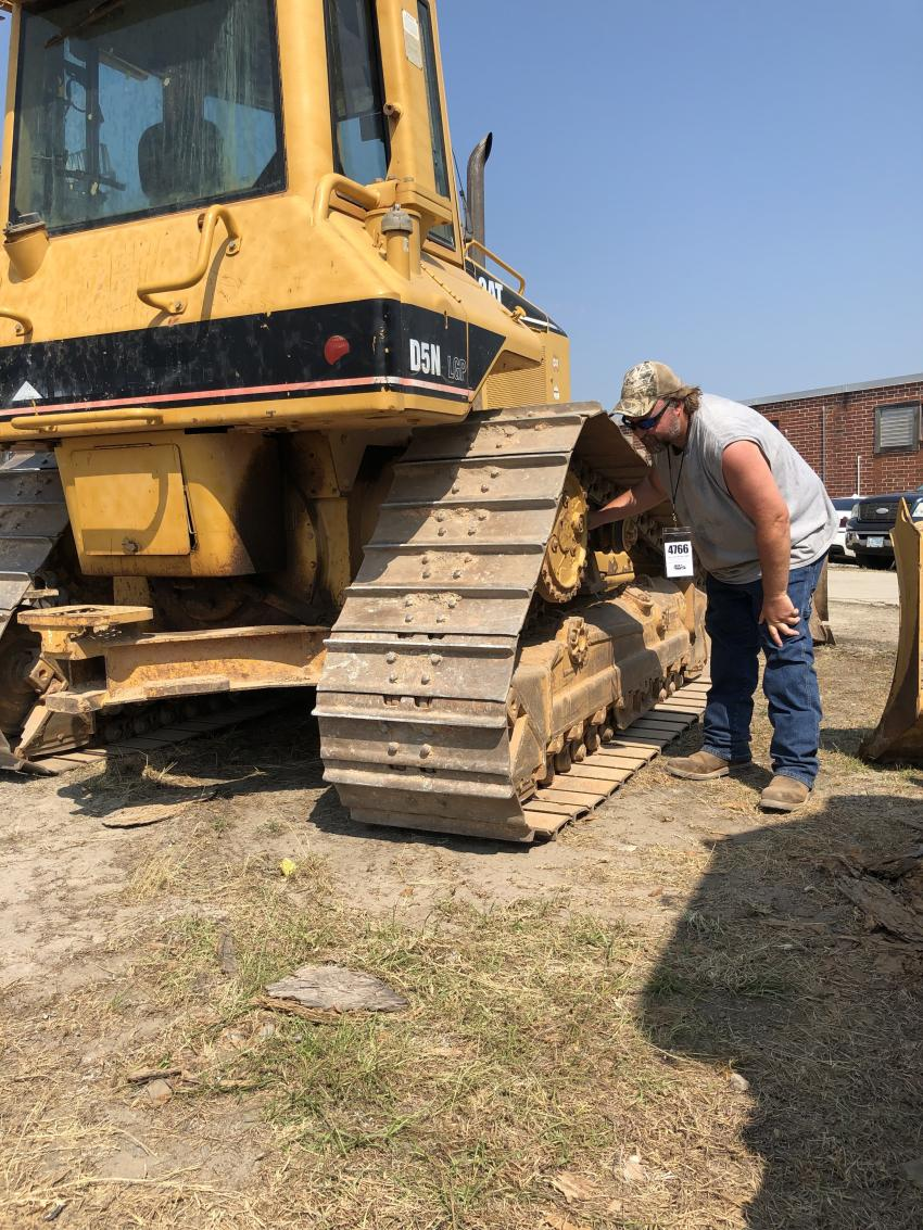 Scott Livingston of Twin Oaks Land Clearing in Cross Hill, S.C., is just starting his business and was looking for dozers and excavators. Here Scott is inspecting the undercarriage wear on this Cat D5N LGP.
