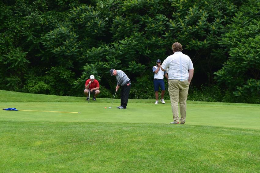 Bill Tucker of Komatsu Northeast putts on hole 18 as the rest of his team — Pat Mollo and Adam Wegener of Komatsu Financial and Andy Jett of Komatsu Northeast — watches in anticipation.