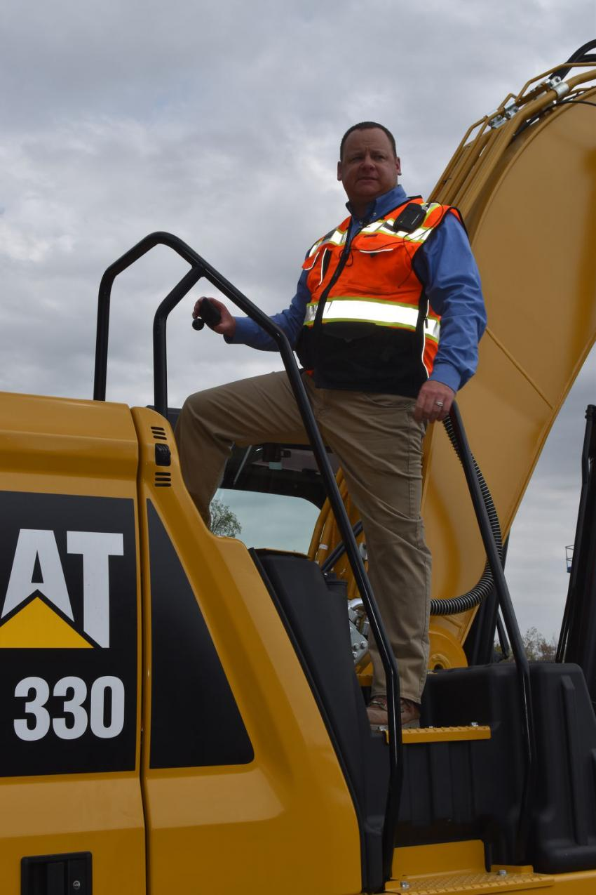 Jason Hibbard of Milton CAT directs the attention of attendees to the improved service and maintenance features of the Next Generation CAT 330 excavator