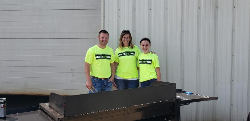 (L-R): Bryan Schlangen, midwest sales, with Danielle Bauer, wife of Joel Bauer, owner of Midsota Manufacturing, and Joel's daughter, Cameron, cook up brats for lunch.