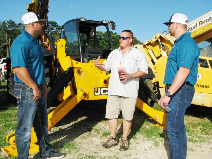 Guy Selinka (L) of Streamline Financial Services and his company's newest representative, Nathan Clark (R), talk to David Raum of McGrew Equipment, York, Pa., about Streamline's equipment financing programs and offers.
