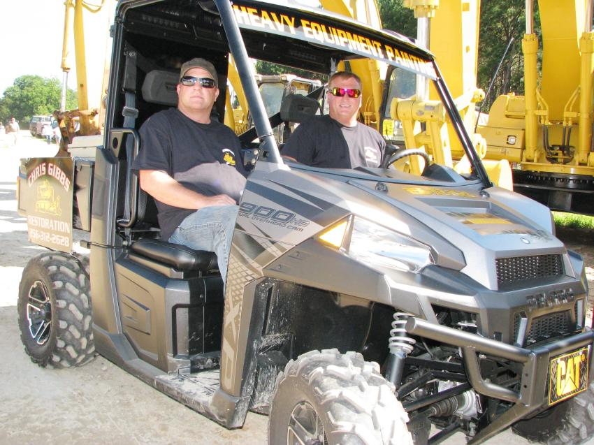 Sean Kimberly (L) and Chris Gibbs of Chris Gibbs Restoration, Tallapoosa, Ga., roll around the auction yard in their Polaris and check out the quality paint and restoration work their company has done on some of the machines being auctioned.