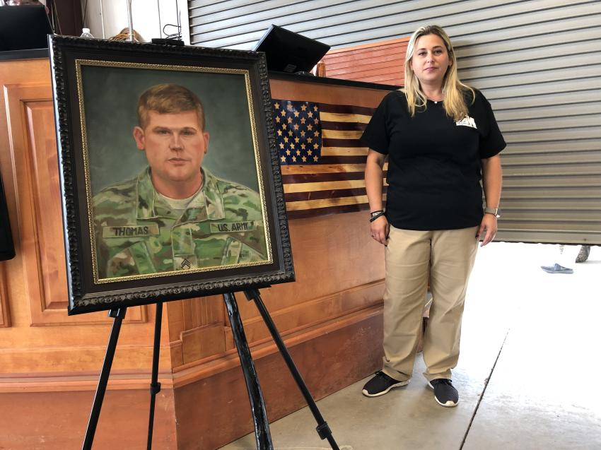 "Tia Thomas poses next to a painting of her late brother, SFC Matthew Bradford ""Brad"" Thomas, and the handmade wooden American flag that was sold to benefit the Tragedy Assistance Program (TAPS) in his memory."