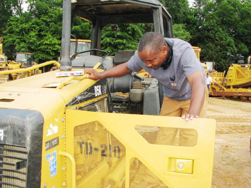 Digging in to the power plant of a Cat dozer during his machine inspection is independent contractor Christopher Jones of Union Town, Ala.