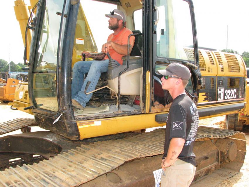 Jason Miller (in cab) and his son, Dawson Miller, contractors/farmers based in McKenzie, Ala., give a Cat 322CL excavator a once over before consideration of bidding on it.