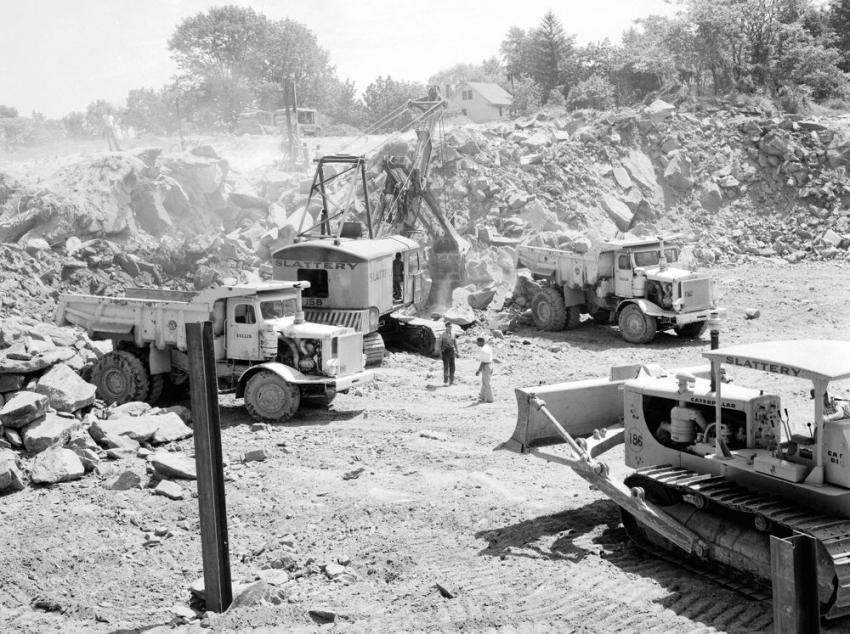 A Northwest 80-D shovel flanked by Euclid 22-ton end dumps excavates a rock cut near James Street in Greenwich, Conn., on June 20, 1956. The cut dozer in the foreground is a Caterpillar D8. A pair of Jaeger 600 cfm air compressors power rock drills on top of the cut.