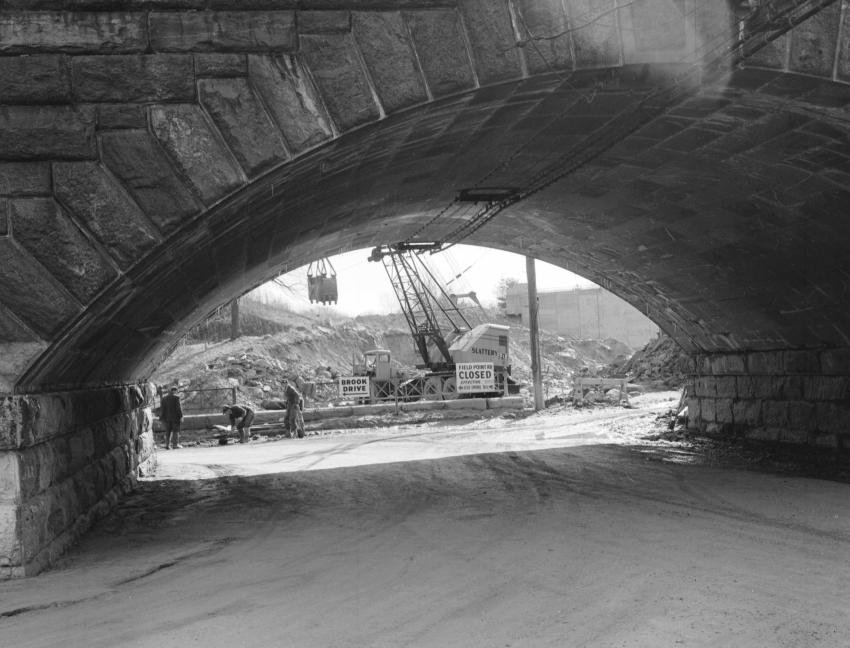 A P&H truck crane equipped with a clamshell bucket is framed by a stone arch RR overpass.