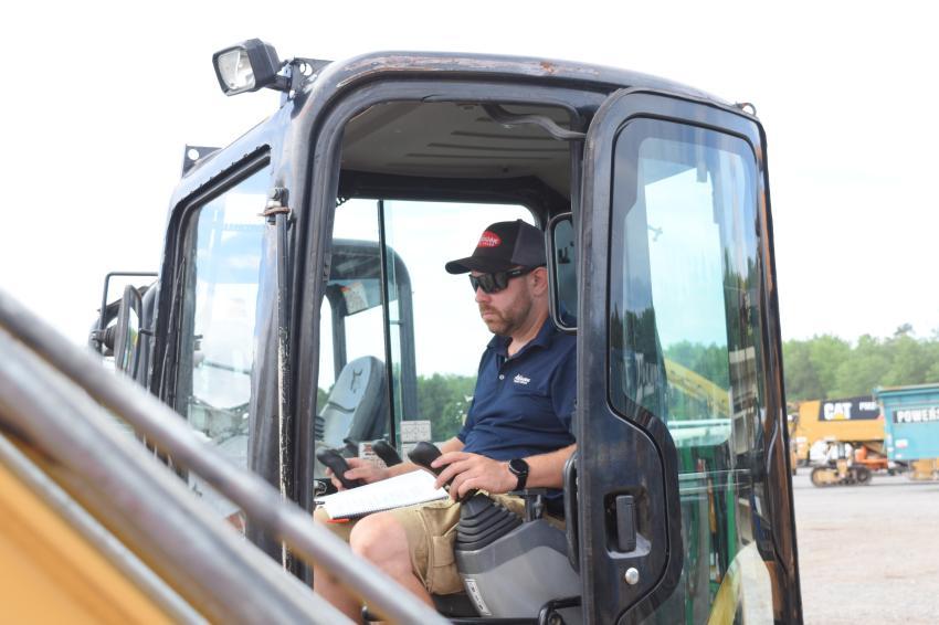 Jason Palmer, sales representative of Atkinson Truck Sales Inc., Chatham, Va., checks out a few mini-excavators.