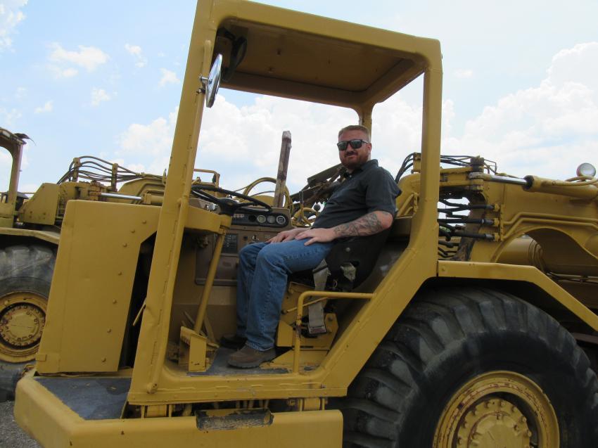 Equipment & Trucks Inc.'s Ryan Ruby considers a bid on this Caterpillar 613C elevating motor scraper at the auction.