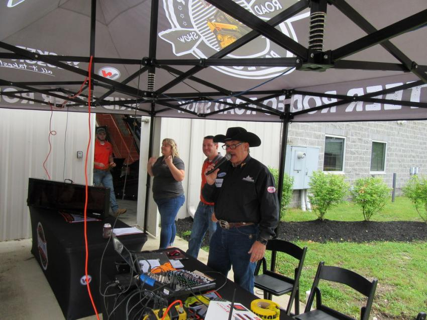 Professional rodeo announcer Joe Coalter calls out the action as contestants compete in the skid steer rodeo event.