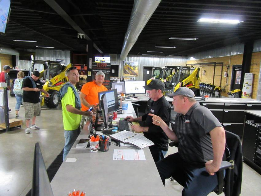 (L-R): Taking care of business during the event, Elite Tree Service's Jason Lynn and David Messer consult Mike Jaggers and Greg Cox at the Franklin Rental counter about equipment for an upcoming job.