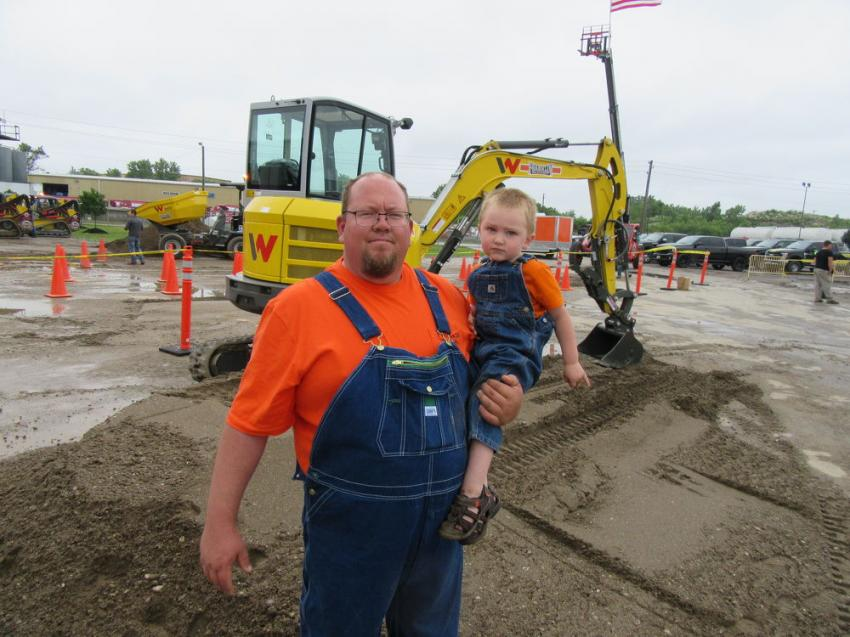 Tom Loudermilk of Gravel Guy Excavating and his son and partner, Tyler, admire this Wacker Neuson EZ36 compact excavator at the event.