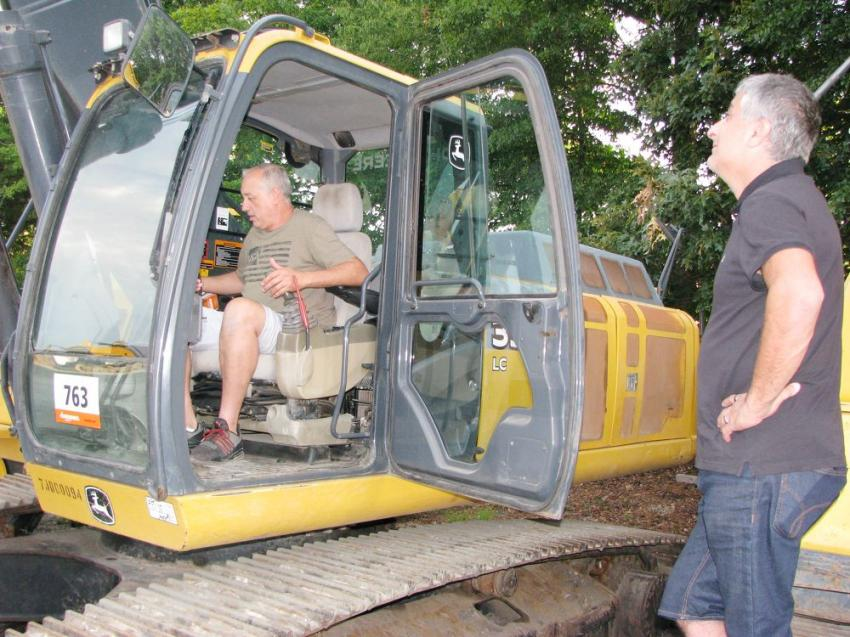 Inspecting a John Deere 350G LC excavator of interest are Marcello Cora (in cab) of Tioetro Pro Flooring, Orlando, Fla., and Jamil Swaid of JS Flooring, Orlando, Fla.