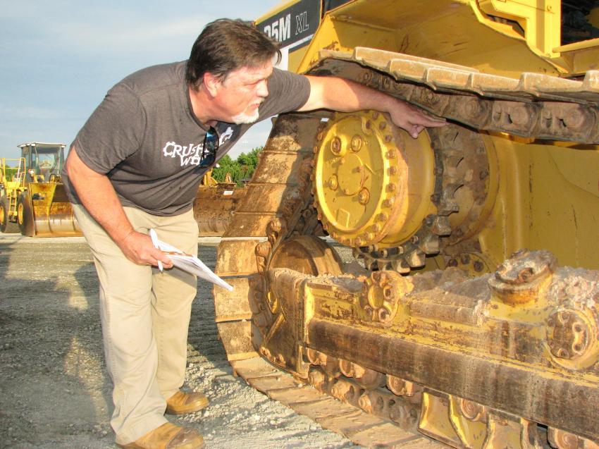 Checking the undercarriage of Cat D5M XL dozer is Scott Webb of Wholesale Equipment Sales in Birmingham, Ala.