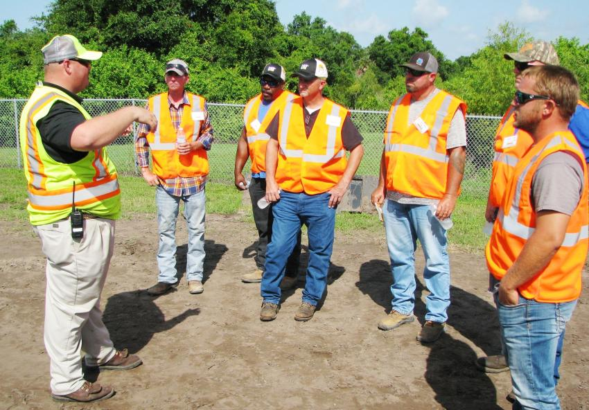 Bryce McGuire (L), one of Ring Power's machine demo specialists, provides complete details and rules for the compact track loader competition to some of the competition finalists.