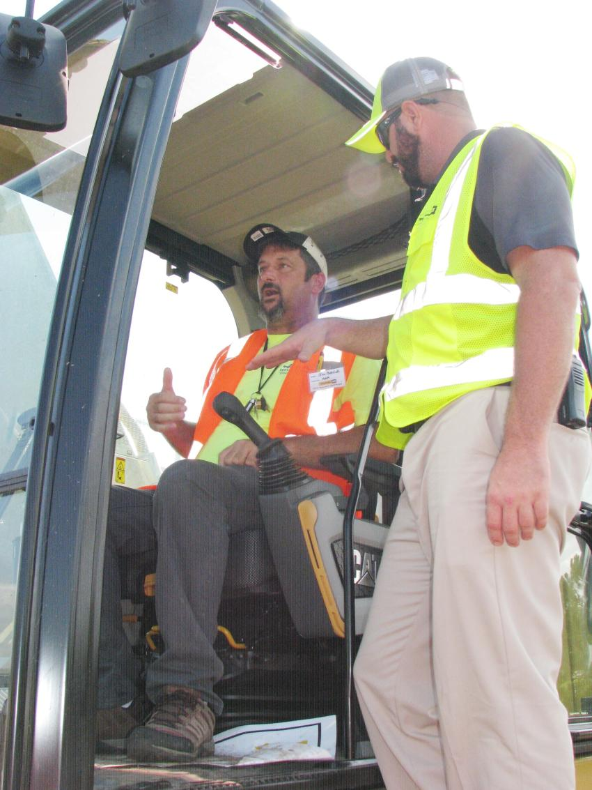 Contestant Jim Schlick (L) of AAA Services, Clearwater, Fla., receives additional instruction on operating a Caterpillar 336 excavator from Ring Power machine demo specialist Blake Conwell.
