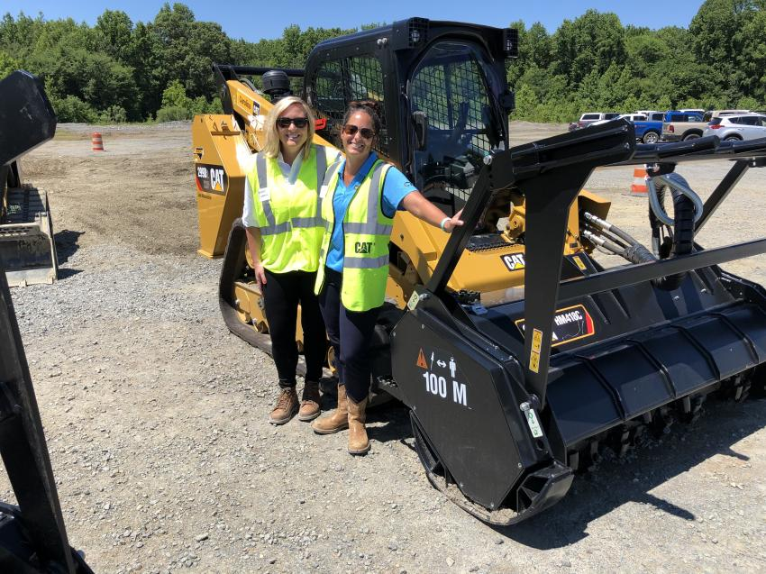 Kristin Gaskil (L) of Caterpillar and Shae Dwyer of CTE are in front of the Cat 299D2 compact track loader with a Cat HM418C high flow XHP hydraulic mulcher attachment.