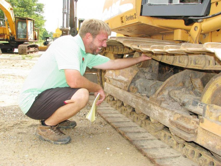 Inspecting the undercarriage of a Case 650K dozer is Jason Lambert of Lambert Equipment, Samson, Ala.