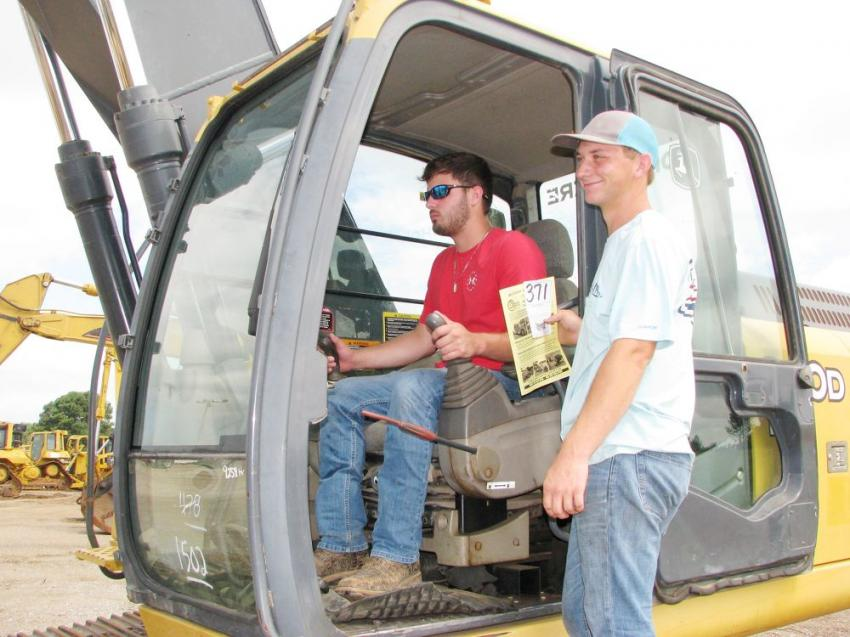 Testing the operation of a Deere 240D LC excavator are Jonathan Bullard (L) and Gage Montgomery of Montgomery Tree Service, Duck Hill, Miss.