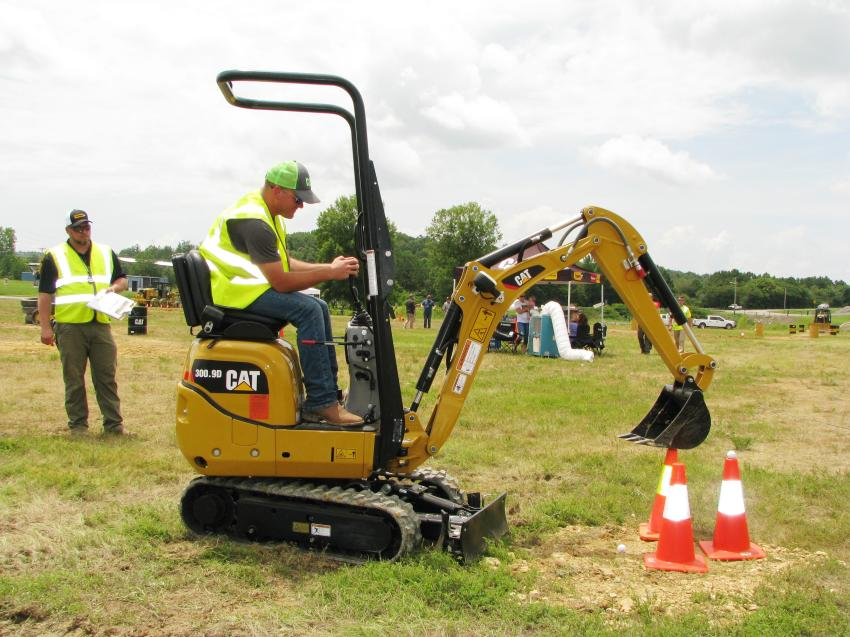 James Geeslin (L) of Thompson Tractor's Birmingham, Ala., location watches as PJ Phillips of Alabama Coal Cooperative, Parish, Ala., does a practice run on the Cat 300.9D mini-excavator golf challenge.