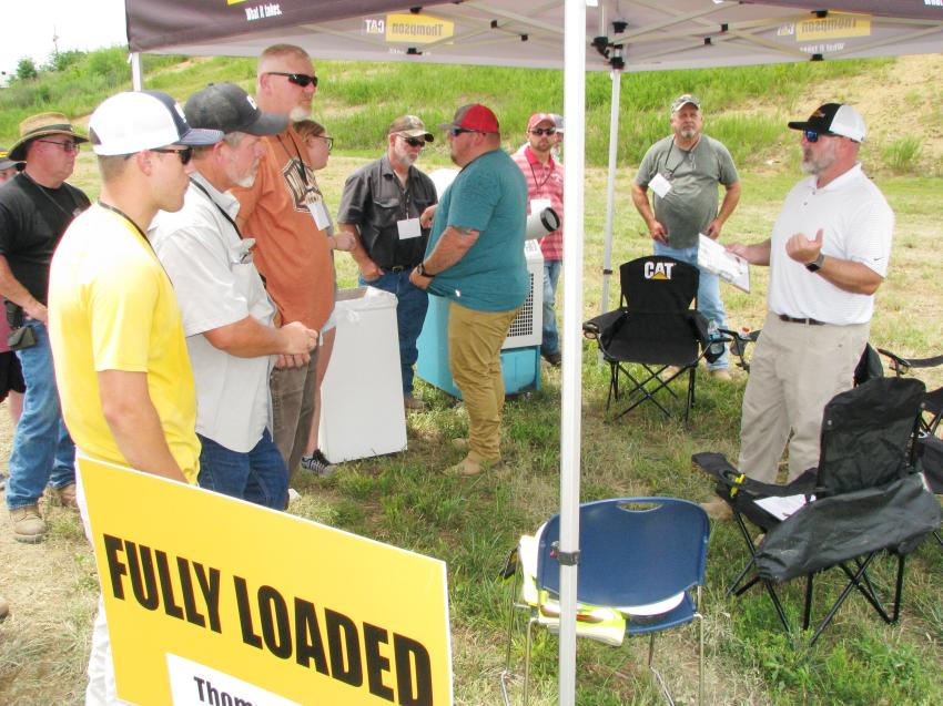 Kevin Moro (far R), Thompson Tractor technical services manager, goes over the rules of the Fully Loaded event with a group of registered contestants.