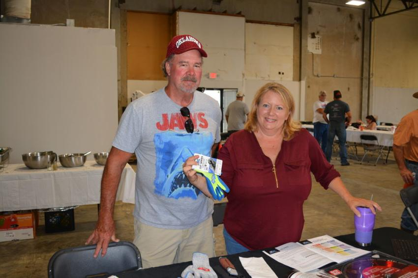 Sara Radcliffe promotes Grip Rite's line of cut-proof gloves to John White, a self-employed contractor from Muskogee. Whitestar Machinery is a Grip Rite dealer.