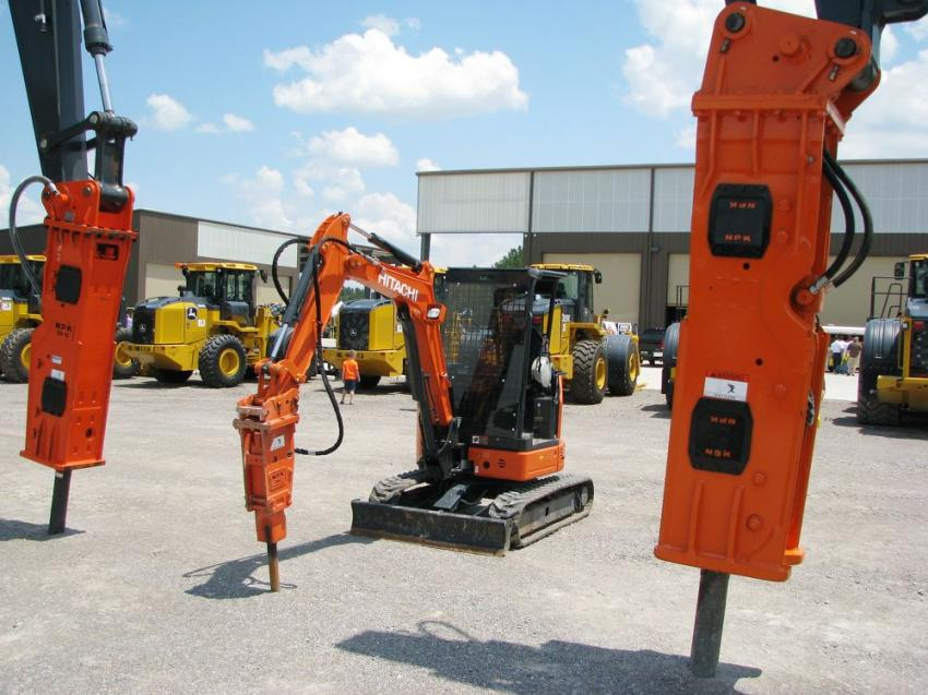 A display of John Deere and Hitachi carrier machines with NPK hammers, in both full-sized and mini machine configurations.