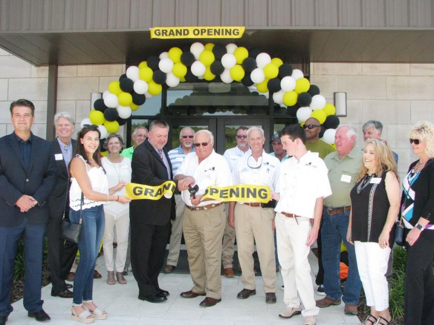 Wielding the big scissors and performing the ceremonial cutting of the ribbon was the mayor of Graysville, Ala., Julio Davis, and Gene Taylor, owner of Warrior Tractor, flanked by dignitaries and key staff members of Warrior Tractor.