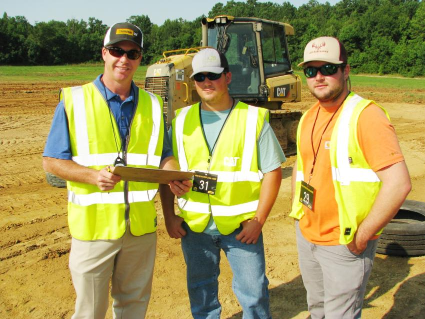 (L-R): Thompson Tractor's Derick Freeman goes over the rules of the Cat dozer event with Dylan Moseley and Colton Scott of Operating Engineers — Local 312, Bessemer, Ala.