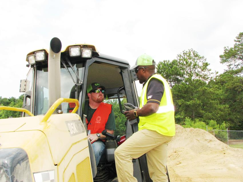 Chris Myrick (in cab) of IUOE Local 312, Bessemer, Ala., receives complete instruction on the Cat dozer challenge from Eugene Mealing Jr., Thompson Tractor's Certified Cat dealer operator/task trainer.