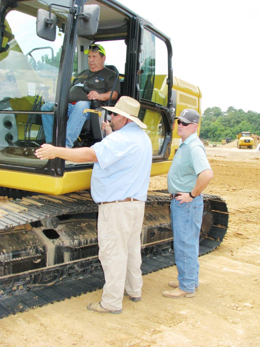 Clayton Walley (below left), Thompson Tractor certified dealer instructor, provides in depth instruction on the Cat 320 excavator challenge to a couple of registered challenge participants.