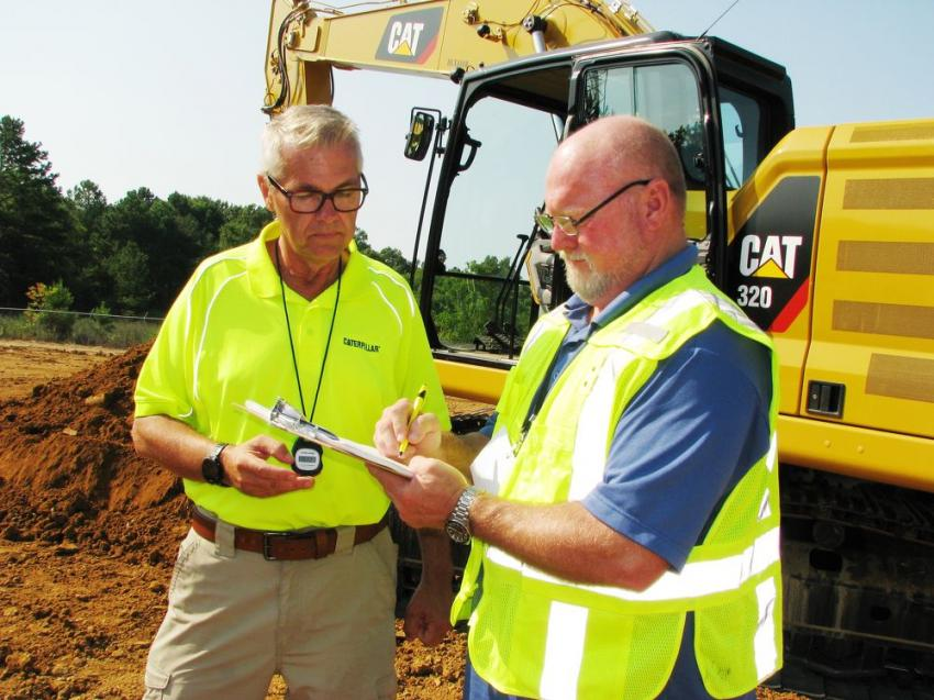 Lee Smith (R), apprenticeship coordinator of the International Union of Operating Engineers — Local 312 in the Birmingham, Ala., area, signs off on his timing on the Cat 320 excavator challenge with Scott Suttle of Thompson Tractor.