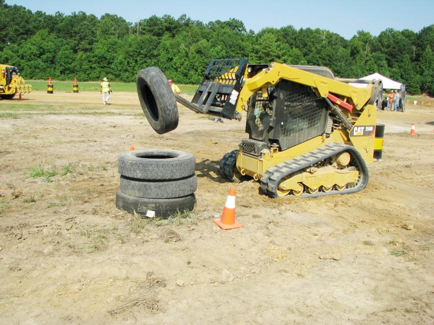 """Making """"clean work"""" of stacking tires in the Cat 259D compact track loader challenge is Justin Pickle of Charles Pickle Septic Tank, Birmingham, Ala."""