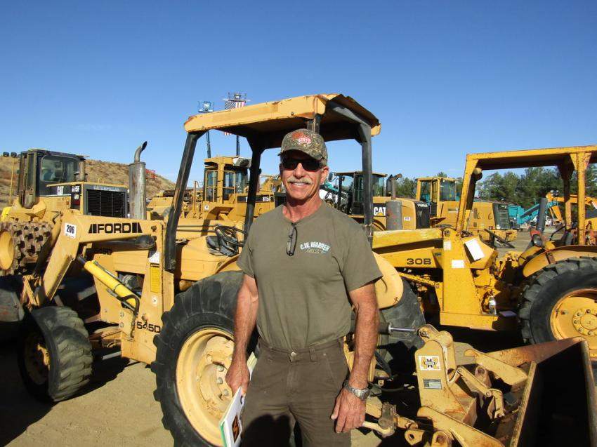 Clif Warren, owner of Warren Framing, Camarillo, Calif., inspects this Ford 545D skip loader.