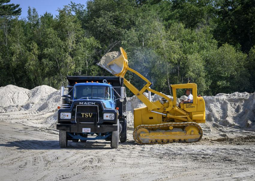 A Rockbuster member loads a dump truck using a 1966 Caterpillar 955H track loader.